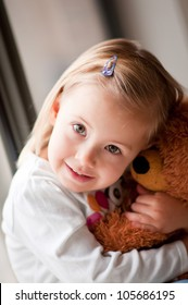 Closeup portrait of adorable toddler girl cuddling with a teddy bear