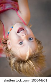 Closeup portrait of adorable toddler girl hanging upside down