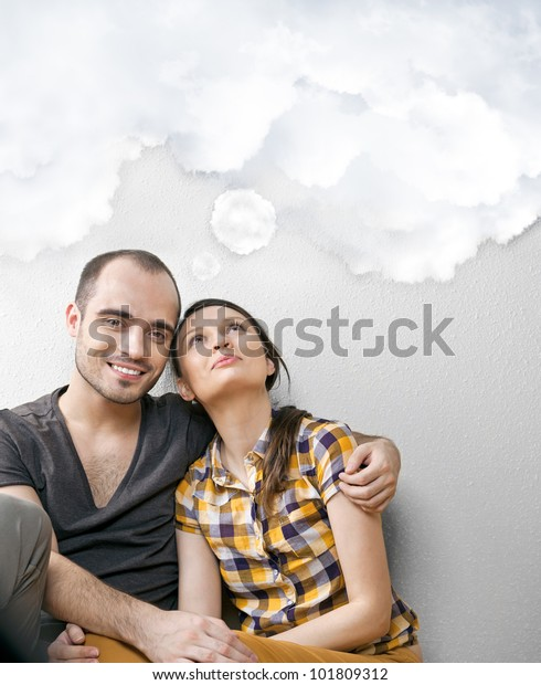 Closeup portrait of adult couple sitting on floor at their apartment and dreaming about something. Blank cloud balloon overhead for your text. Planning future concept