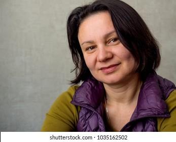 Close-up portrait of an adult happy brunette woman.