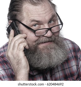 Closeup portrait of an adult male with a beard, calling by mobile phone