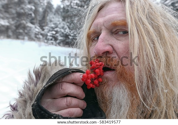 closeup portrait adult male with a beard with viburnum berries in the winter forest
