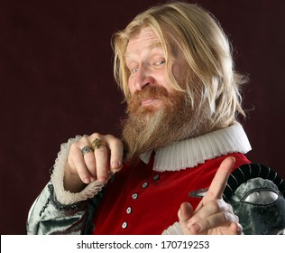 close-up portrait of an adult male with long blond hair beard and mustache in medieval costume studio on a burgundy background