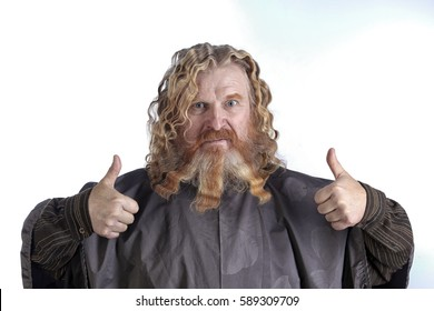 closeup portrait of an adult red-haired man with long wavy hair and beard on a white background