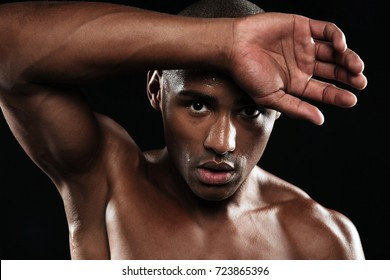 Close-up portrait of afro american sports man, resting after workout, wipes sweat from his forehead, isolated on black background