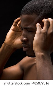 Closeup portrait of Afro-American man having headache in studio. Handsome man with short hair looking away and touching his head.