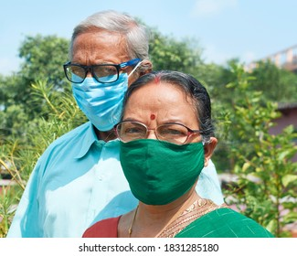 Closeup portrait of an aged Indian couple, both wearing face mask, for prevention of coronavirus infection. The woman is dressed in traditional Bengali sari. Shot in Kolkata, India.
