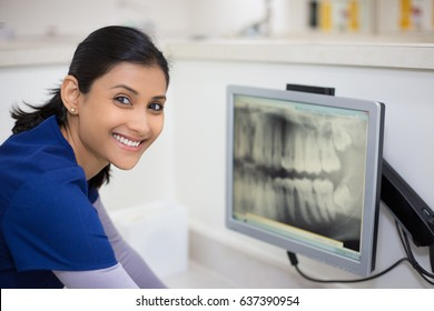 Closeup portrait of allied health dental professional in blue scrubs examining dental x-ray on computer screen, isolated dentist office