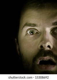 Close-up portrait of amazed guy in the dark