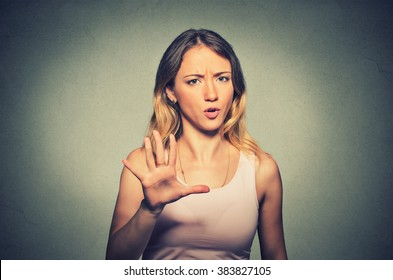 Closeup portrait of angry annoyed woman raising hand up to say no stop right there isolated on gray background. Negative human emotion facial expression