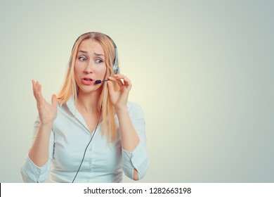 Closeup portrait angry business blonde woman, corporate employee hands in air aggravated talking on headset isolated light green yellow background. Negative emotions, facial expressions, reaction