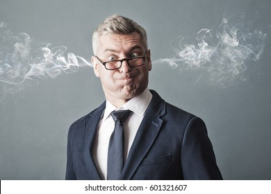 Closeup portrait of angry businessman, blowing steam coming out of ears, about to have nervous breakdown  on gray background. Negative human emotions facial expression feelings attitude