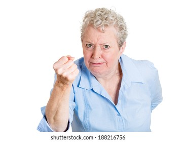 Closeup portrait, angry, cranky, upset, senior mature woman, business worker, fist up about to give you knuckle sandwich, isolated white background. Negative human emotion facial expression feeling