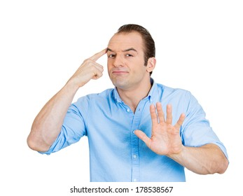 Closeup portrait of angry frustrated sarcastic funny looking business man gesturing with finger against his temple are you crazy, no way, not true isolated on white background. Face expression emotion