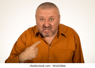 Closeup portrait of angry, mad, unhappy man pointing at himself asking you mean me, you talking to me, isolated on white background. Negative human emotion facial expression