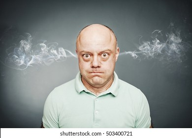 Closeup portrait of angry man, blowing steam coming out of ears, about to have nervous breakdown isolated gray background. Negative human emotions facial expression feelings attitude