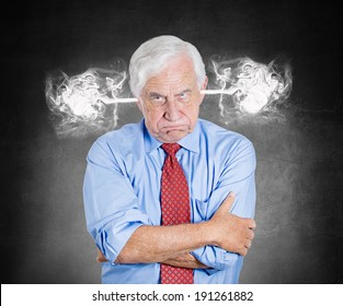 Closeup portrait angry senior business man, blowing steam coming out of ears, about to have nervous atomic breakdown, isolated black background. Negative emotions, facial expression, feeling, attitude