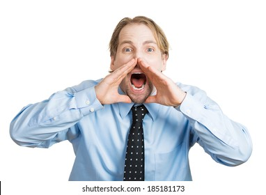 Closeup portrait angry, upset, young man, worker, mad employee, funny looking business man, hands to open mouth yelling, isolated white background. Negative emotions, facial expression, reaction