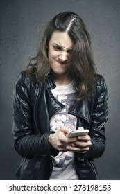Closeup portrait angry young girl looking at phone seeing bad news or photos with disgusting emotion on her face texture background. Human emotion, reaction, expression