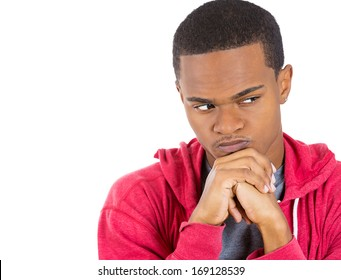 Closeup portrait of angry young man thinking daydreaming deeply about something, pissed off, chin on hands looking away, isolated on white background. Negative emotion facial expression feeling