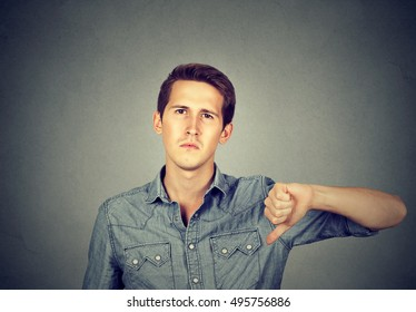 Closeup portrait angry young man showing thumbs down sign, in disapproval isolated on gray background. Negative human emotion facial expression feelings