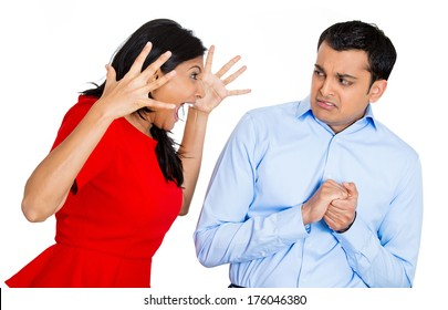 Closeup portrait of angry young woman screaming yelling shouting at scared afraid in fear face man, isolated on white background. Negative emotion facial expression feelings, reaction, situation.