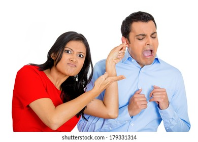 Closeup portrait of angry young woman pulling ear lobe of surprised shocked in pain hurting funny man, isolated on white background. Negative emotion facial expression feelings, reaction, situation.