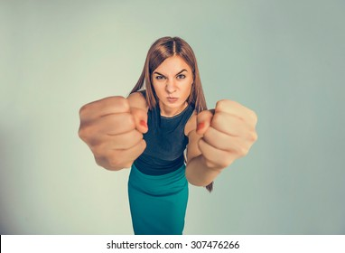 Closeup portrait angry young woman showing fists about to punch hit someone or to have nervous atomic breakdown isolated black background. Negative human emotions facial expression feelings attitude