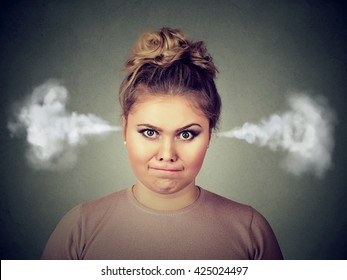 Closeup portrait of angry young woman, blowing steam coming out of ears, about to have nervous atomic breakdown isolated on black background. Negative human emotion facial expression feelings attitude