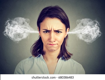 Closeup portrait of angry young woman, blowing steam coming out of ears isolated gray background. Negative human emotions facial expression feelings