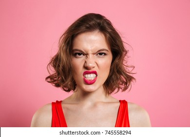 Close-up portrait of angry young woman with red lips looking at camera, isolated on pink background