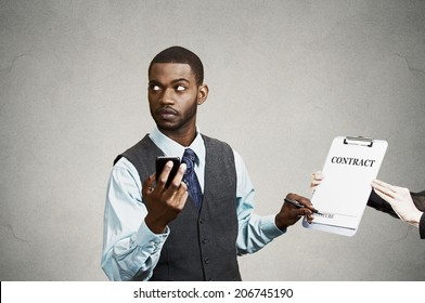 Closeup portrait annoyed skeptical sneaky businessman signing contract without looking at document, corporate executive holding mobile smart phone isolated grey black background. Human face expression
