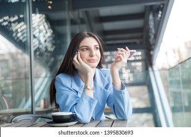 Closeup portrait of annoyed woman holding phone to side rejecting call, hispanic girl wearing formal blue suit and white shirt sitting at a table on a cafe terrace balcony outside staircase background