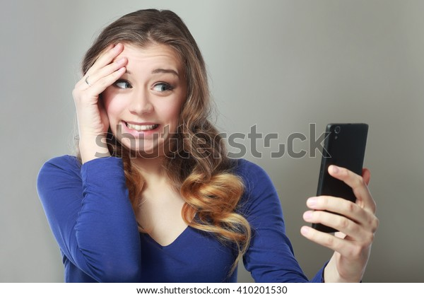 Closeup portrait anxious scared young girl looking at phone seeing bad news photos message with disgusting emotion on her face isolated on gray wall background. Human reaction