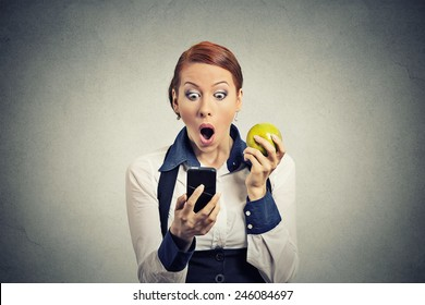 Closeup portrait anxious shocked young business woman looking at phone seeing bad news or photos with disgusting emotion on her face isolated grey wall background. Human emotion, reaction, expression