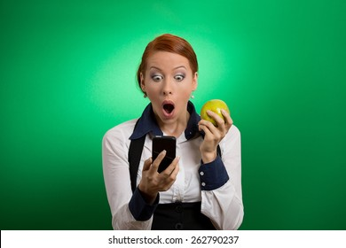 Closeup portrait anxious shocked young business woman looking at phone seeing bad news or photos with disgusting emotion on her face isolated green background. Human emotion, reaction, expression