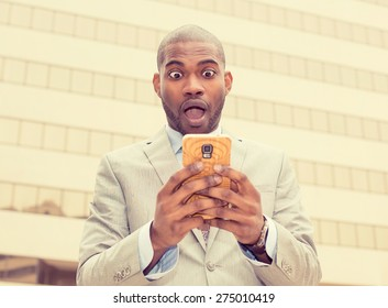 Closeup portrait anxious young business man looking at phone seeing bad news or photos with disgusting emotion on his face isolated outside city background. Human emotion, reaction, expression