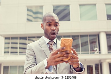 Closeup portrait anxious young business man looking at smart phone seeing bad news or photos with disgusting shocked face expression isolated outside city background. Human emotion, reaction