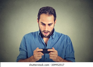 Closeup portrait anxious young man looking at phone seeing bad news or photos with scared emotion on his face isolated on gray wall background. Human emotion, reaction, expression