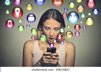 Closeup portrait anxious young woman looking at smart phone multiple app icons flying away from screen. Human face expression emotion