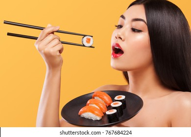Closeup portrait of asian woman eating sushi and rolls on a yellow background.