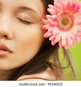 Closeup portrait of attractive asian brunette young woman with pink flower in hair