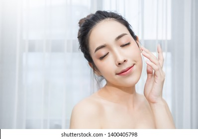 Closeup portrait of attractive asian woman with fair perfect healthy glow skin using cleaning on her face, young beautiful girl with pretty smile on her face. Beauty clinic skincare spa concept