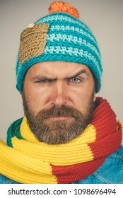 Closeup portrait attractive bearded man in warm knitted hat, scarf. Health, beauty and people concept - portrait of serious caucasian man with beard in fashionable scarf and hat. Male winter fashion.