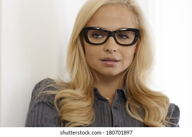 Closeup portrait of attractive blonde woman with black framed glasses.
