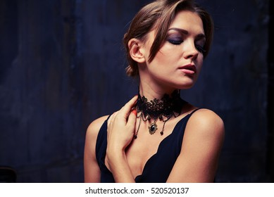 Close-up portrait of attractive brunette looking off camera and hand touching neck. Lace choker necklace add a bit of mystery to charming woman