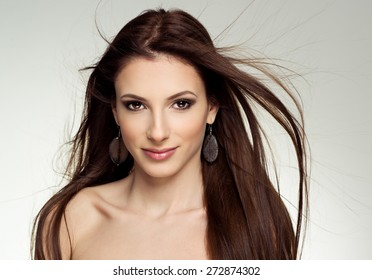 Close-up portrait of attractive Caucasian female salon model with flying hair. Young pretty fashion girl wearing stony earrings posing in studio.