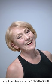 closeup portrait of attractive caucasian smiling mature woman blond on gray background studio shot looking at camera head and shoulders