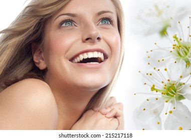 closeup portrait of attractive  caucasian smiling woman blond isolated on white studio shot lips toothy smile face hair head and shoulders looking up blue eyes tooth spring flowers aroma