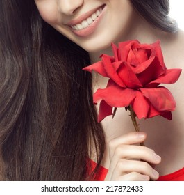 closeup portrait of attractive  caucasian smiling woman brunette isolated on white studio shot lips toothy smile face hair head and shoulders looking at camera tooth  red rose flower